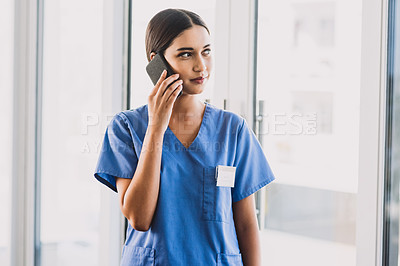 Buy stock photo Cropped shot of an attractive young nurse making a phone call while standing in her office during the day