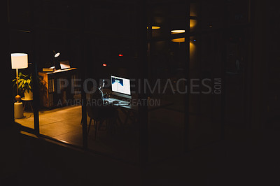 Buy stock photo Rearview shot of a young businesswoman working on a computer in an office at night
