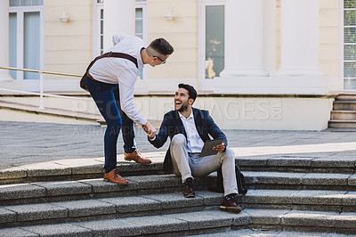 Buy stock photo Shot of two young businessmen meeting on steps in a city