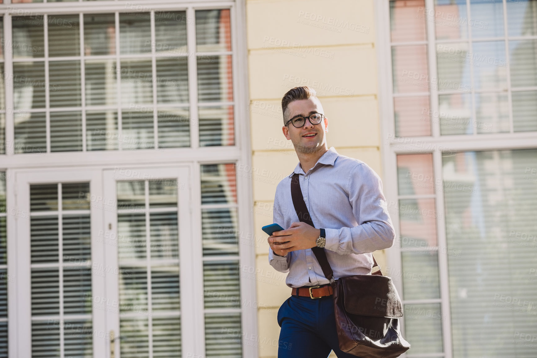 Buy stock photo Shot of a young businessman using a smartphone while walking through the city