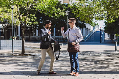Buy stock photo Shot of two young businessmen celebrating an achievement outdoors