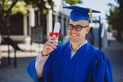 Buy stock photo Shot of a happy young man holding his diploma on graduation day