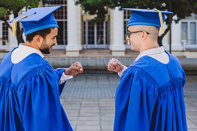 Buy stock photo Shot of two young men fist bumping each other on graduation day