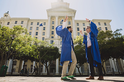 Buy stock photo Shot of two young men celebrating on graduation day