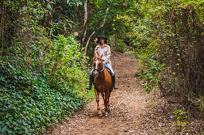 Buy stock photo Shot of a young woman riding a horse in a forest