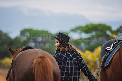 Buy stock photo Shot of a young woman walking with two of her horses on a farm