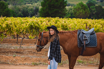 Buy stock photo Shot of a young woman walking with her horse on a farm