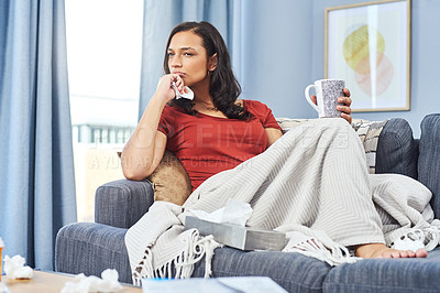 Buy stock photo Shot of an attractive young woman looking thoughtful while feeling sick at home