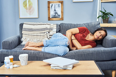 Buy stock photo Full length shot of an attractive young woman suffering from stomach cramps while lying on her couch at home