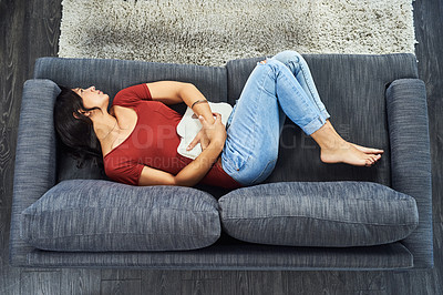 Buy stock photo High angle shot of an attractive young woman suffering from stomach cramps while lying on her couch at home