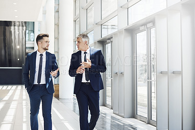 Buy stock photo Cropped shot of two handsome businessmen having a discussion while walking through the office during the day