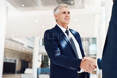 Buy stock photo Cropped shot of a handsome mature businessman shaking the hand of an unrecognizable colleague while in the office