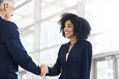 Buy stock photo Cropped shot of an attractive young businesswoman shaking hands with her mature colleague while in the office during the day