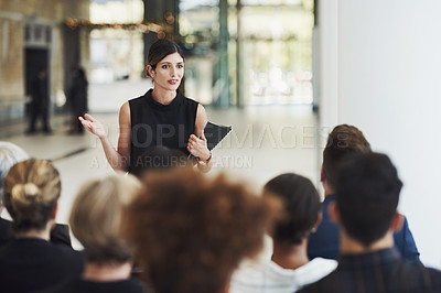 Buy stock photo Shot of a young businesswoman delivering a speech during a conference