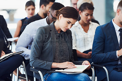 Buy stock photo Cropped shot of a businesswoman making notes during a conference