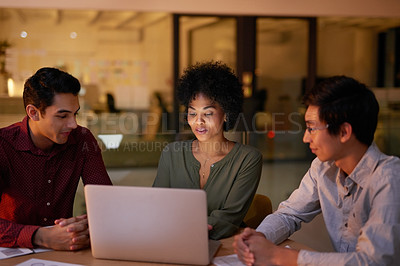 Buy stock photo Cropped shot of a group of young businesspeople using a laptop while working late in a modern office