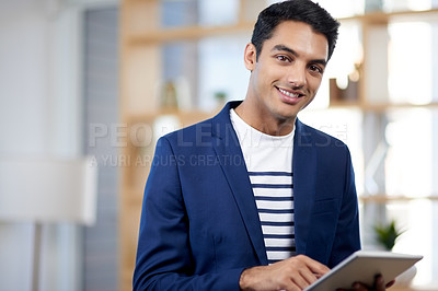 Buy stock photo Portrait of a handsome young businessman using a digital tablet in an office