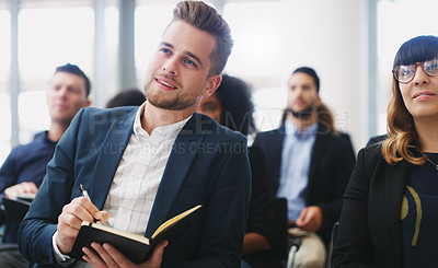 Buy stock photo Shot of a young businessman taking down notes while sitting in the audience of a business conference