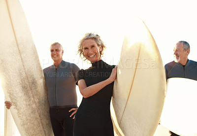 Buy stock photo Cropped portrait of a group of happy senior people holding their surfboards on the beach before surfing during the day