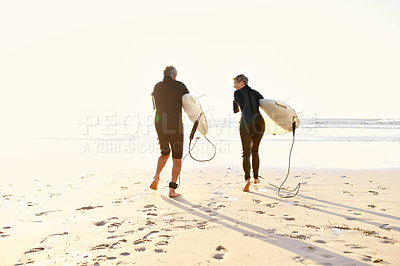 Buy stock photo Full length shot of a happy senior couple holding their surfboards and walking towards the sea to surf