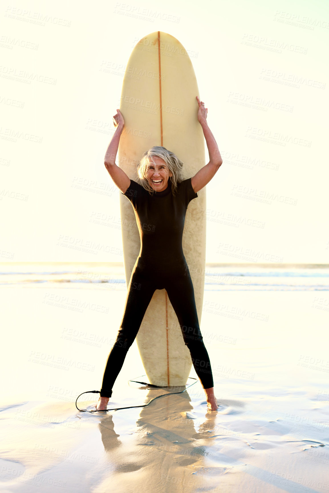 Buy stock photo Full length portrtait of a happy senior woman standing and posing with her surfboard while on the beach