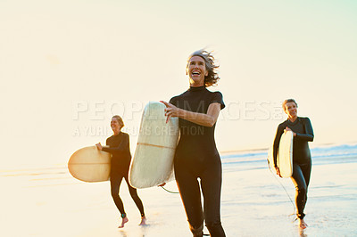 Buy stock photo Full length shot of three happy senior women holding their surfboards and walking towards the beach after their daytime surf