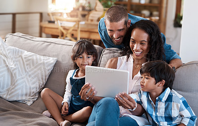 Buy stock photo Shot of a family of four watching something on a digital tablet