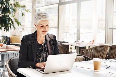 Buy stock photo Shot of a mature businesswoman using a laptop while sitting in an airport cafe