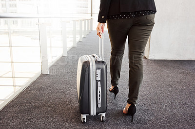 Buy stock photo Cropped shot of a businesswoman walking through an airport with her luggage