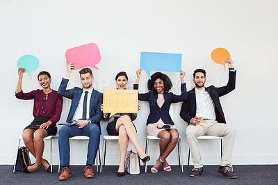 Buy stock photo Studio portrait of a group of young businesspeople holding speech bubbles while sitting in a row against a white background