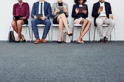Buy stock photo Studio shot of a group of unrecognizable young businesspeople using wireless technology while sitting in line against a white background