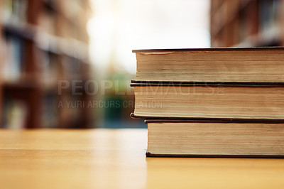 Buy stock photo Shot of a stack of books on a table in a library