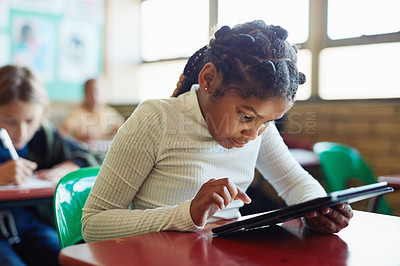 Buy stock photo Shot of a young girl using a digital tablet at her desk in a classroom