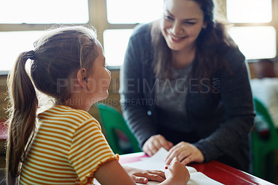 Buy stock photo Shot of a young girl being assisted by her teacher in a classroom