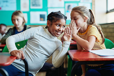 Buy stock photo Shot of two young girls whispering to each other in a classroom