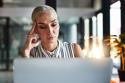 Buy stock photo Shot of a beautiful young businesswoman looking stressed out while working late in her office