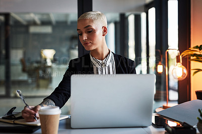 Buy stock photo Shot of an attractive young businesswoman writing on a notepad while working late in her office