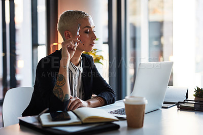 Buy stock photo Shot of an attractive young businesswoman using a laptop while working late in her office