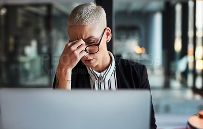 Buy stock photo Shot of a beautiful young businesswoman suffering from a headache while working late in her office