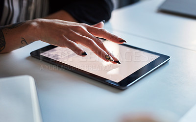 Buy stock photo Shot of an unrecognizable businesswoman using her digital tablet in her office