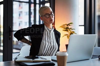 Buy stock photo Shot of an attractive young businesswoman suffering from back pain while working late in her office