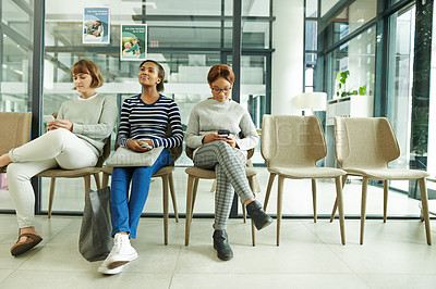Buy stock photo Shot of a group of young women sitting in the waiting room of a clinic