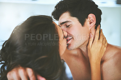 Buy stock photo Shot of an affectionate young couple kissing in their bedroom at home
