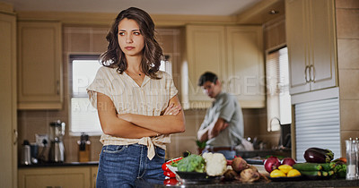 Buy stock photo Shot of a young woman looking upset after a fight with her boyfriend who is standing in the background