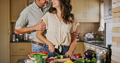 Buy stock photo Shot of a young woman cooking while being embraced by her boyfriend