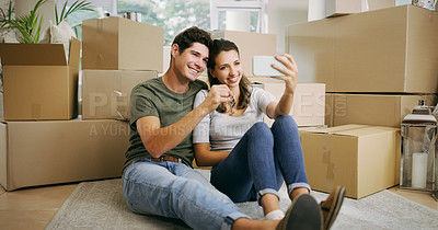 Buy stock photo Shot of a young couple taking a selfie in their new home