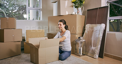 Buy stock photo Shot of a woman unpacking boxes in her new house