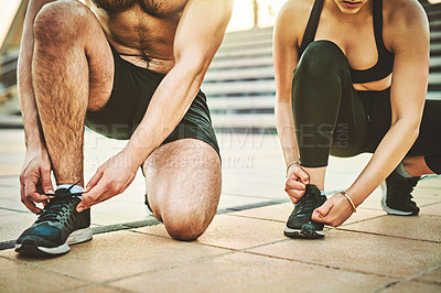 Buy stock photo Closeup shot of two unrecognisable people tying their shoelaces while exercising together outdoors