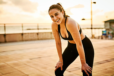 Buy stock photo Portrait of a sporty young woman taking a break while exercising outdoors