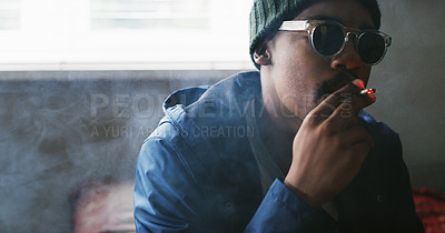 Buy stock photo Shot of a young man smoking a marijuana joint at home